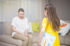 Child daughter congratulates mom and gives her painting. Mum and girl smiling and hugging. Family holiday and happiness. Stock Image