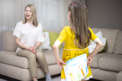 Child daughter congratulates mom and gives her painting. Mum and girl smiling and hugging. Stock Photos