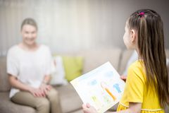 Child daughter congratulates mom and gives her painting. Mum and girl smiling and hugging. Family holiday and happiness. royalty free stock photos