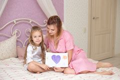 Child daughter congratulates mom and gives her a postcard royalty free stock image