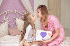 Child daughter congratulates mom and gives her a postcard royalty free stock photography