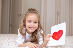 Child daughter congratulates mom and gives her a postcard royalty free stock photos
