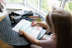 Child daughter painting postcard for mom. Girl sitting at home on table, next lying pink flower for mother. Mother day concept stock photography
