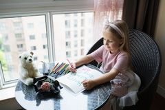 Child daughter painting postcard for mom. Girl sitting at home on table, next lying pink flower for mother. Mother day concept royalty free stock photos