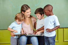 Child day care worker with children. Happy child day care worker with children reading a book in kindergarten Stock Photography
