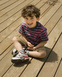 Child on deck. Happy child sitting on a wooden deck Royalty Free Stock Photography