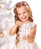 Child decorate Christmas tree. Child holding snowflake to decorate Christmas tree Royalty Free Stock Photos