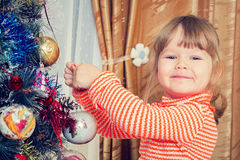 Child decorate the Christmas tree Stock Images