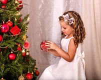 Child decorate on Christmas tree home alone. Stock Images