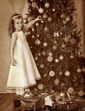 Child decorate on Christmas tree Stock Images