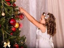 Child decorate on Christmas tree. Stock Photos