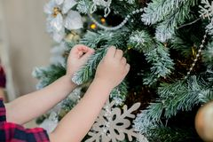 Child decorate a Christmas tree Stock Photos