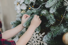 Child decorate a Christmas tree Stock Image