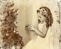 Child decorate Christmas tree . Old photo on yellow paper. Stock Photos
