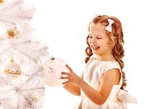 Child decorate white Christmas tree. Royalty Free Stock Image