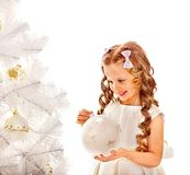 Child decorate white Christmas tree. Royalty Free Stock Photo