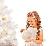 Child decorate white Christmas tree. Royalty Free Stock Photo