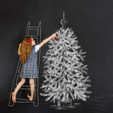 Child decorates a Christmas tree drawing on blackboard. Christma Royalty Free Stock Images