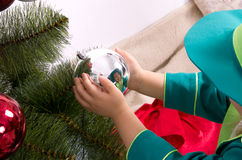 Child decorates a Christmas tree. New Year balls Stock Photo