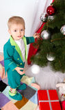 Child decorates a Christmas tree. New Year balls Royalty Free Stock Photo