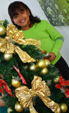 A Child decorating a Christmas tree with baubles Stock Photo