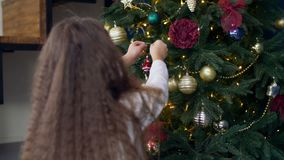 Child decorating Christmas tree with toys stock video
