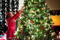 Child decorating Christmas tree. Xmas for kids. Little girl in red knitted Nordic reindeer sweater hanging ornaments on Christmas tree with light, bauble and stock images