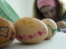 Child decorating Easter eggs. Easter traditions concept: childish drawings on three eggs (shallow depth of field on the eggs), and blurry face of a preschooler Royalty Free Stock Photo