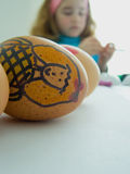 Child decorating Easter eggs. Easter traditions concept: childish drawings on three eggs (shallow depth of field on the eggs), and verry blurred out face of a Stock Images