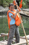 Child is delimiting the bamboo raft Stock Images