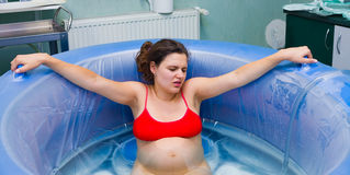 Child delivery in water. Young beautiful woman during labour right before giving birth in water Royalty Free Stock Photos