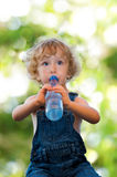 Child in denim suit drinking water Stock Image