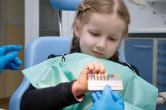 The child dental picks colored fillings. On clinic stock image