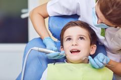 A child with a dentist in a dental office. Dental treatment in a children`s clinic stock photography