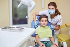 A child with a dentist in a dental office. Dental treatment in a children`s clinic stock image