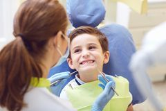 A child with a dentist in a dental office. Dental treatment in a children`s clinic stock photos