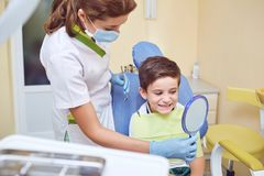 A child with a dentist in a dental office. Dental treatment in a children`s clinic royalty free stock photo