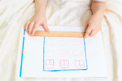 Child designing and measuring a house Royalty Free Stock Images