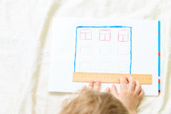 Child designing and measuring a house Royalty Free Stock Photos