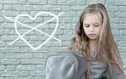Child& x27 ; dessin de s Fille assez triste s'asseyant sur le fond du mur de briques, qui est peint le coeur croisé Photographie stock