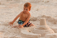 Child destroy sand castle. Child destroy sand castle beach outdoors summer childhood royalty free stock image