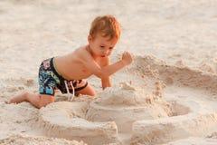 Child destroy sand castle. Child destroy sand castle beach playing summer childhood royalty free stock photo