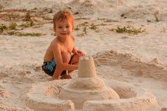 Child destroy sand castle. Child destroy sitting sand castle beach summer childhood stock photos