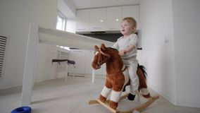 Child development, cute sweet baby boy riding plush horse and smiling at home in room. Child development, cute sweet baby boy riding plush horse and smiling at stock footage