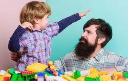 Child development and upbringing. Bearded hipster and boy play together. Dad and child build of plastic blocks. Happy stock photography
