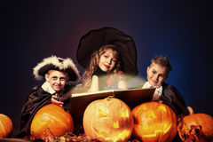 Child devilry. Cheerful children in halloween costumes standing with pumpkins and a book of spells. Over dark background Stock Photo