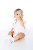 Child in a diaper sitting and sucking finger Stock Images