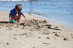 Child digging at the beach. Young boy playing and digging at the beach royalty free stock image