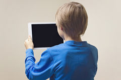 Child with digital tablet computer. Back view. Child using digital tablet computer. Back view. Education, learning, leisure concept Royalty Free Stock Image