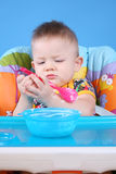 Child dines. A child sits in a chair for feeding and eating Royalty Free Stock Image